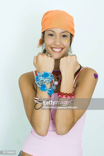 'Teen girl wearing lots of accessories, holding up forearms, smiling at camera, portrait'