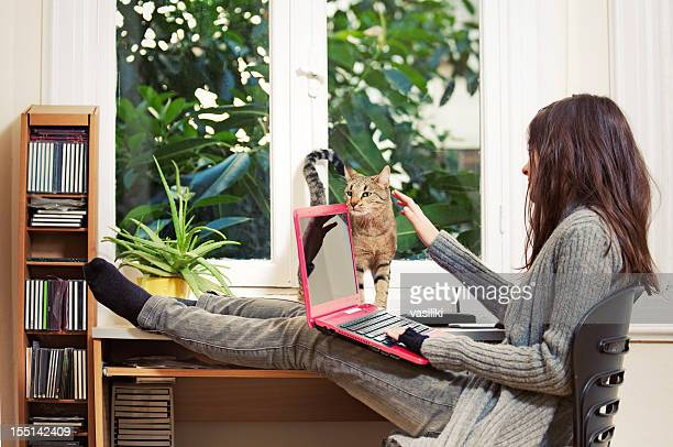 Teen girl with cat and laptop