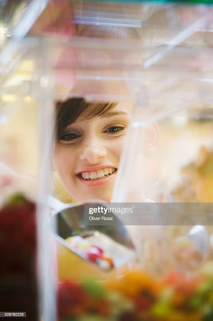 Teen girl with scoop of candy : Stock Photo