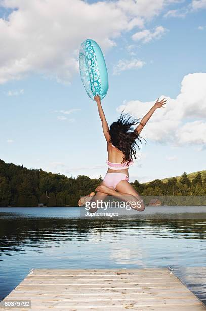 Teen girl with swim ring jumping into lake