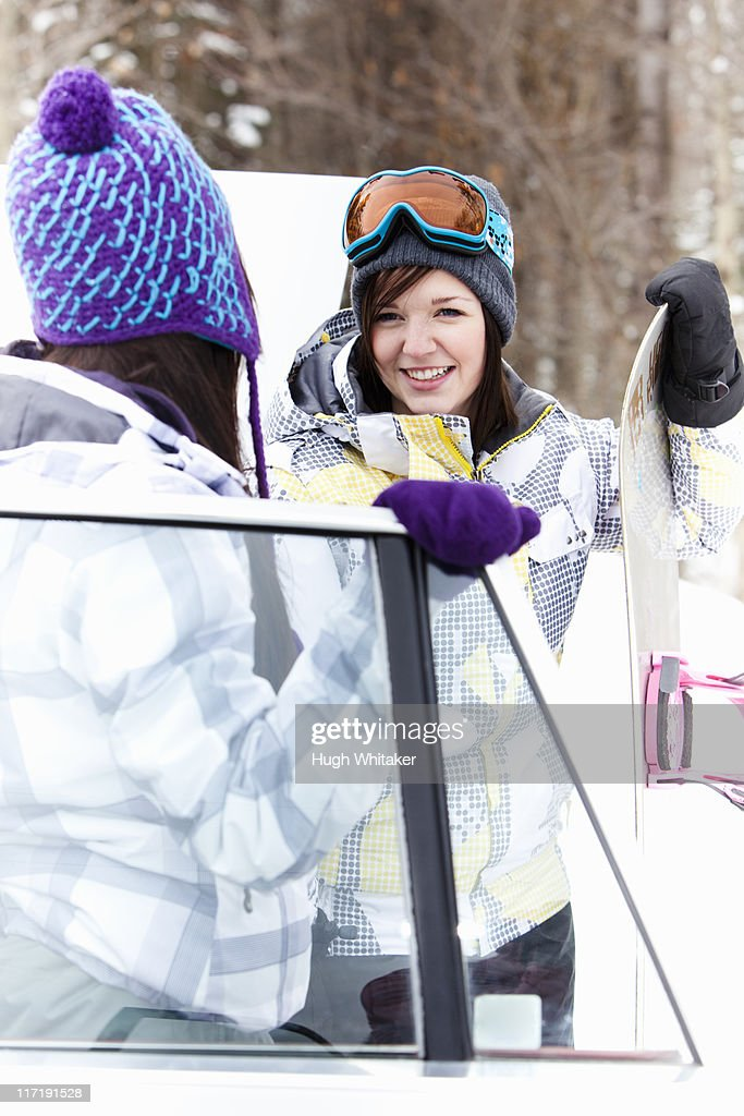 Teen girls by car with snowboard : Stock Photo