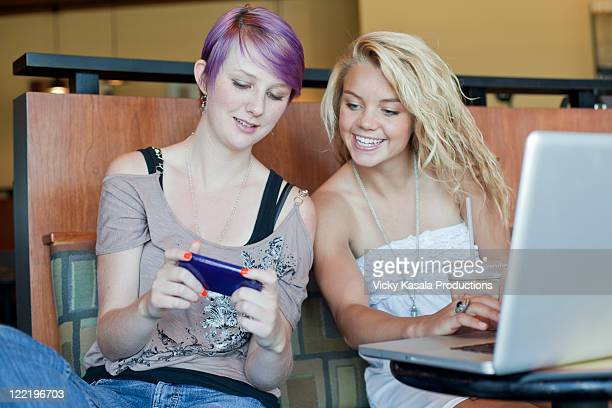 teen girls checking message on cell phone at cafe