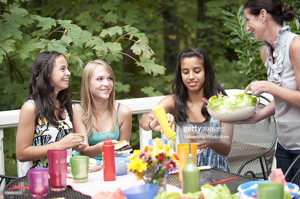 Teen girls eating at outdoor party : Stock Photo