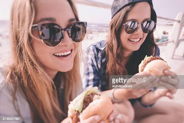 Teen Mädchen Essen Burger zusammen im Freien an einem sonnigen Tag