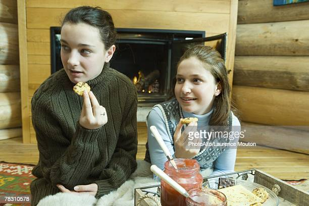 Teen girls having snack by fire place
