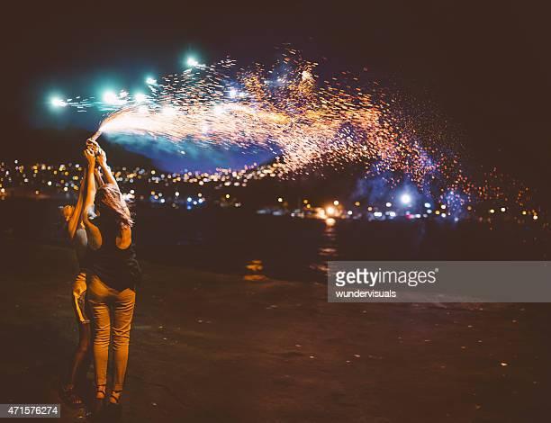Teen girls holding resplandeciente de fuegos artificiales en el puerto de noche