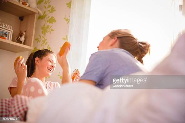 10 代の少女の笑顔とドーナツを食べるのベッドルーム