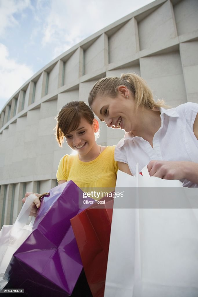 Teen girls looking in shopping bags : Stock-Foto
