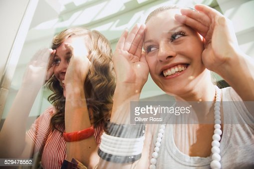 Teen girls looking through shop window : Stock Photo