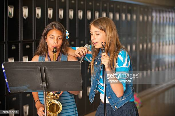 teen girls practicing their music in hallway