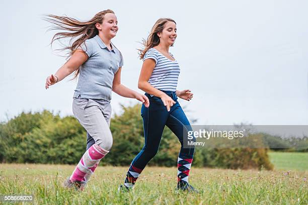 Teen girls running together on summer meadow