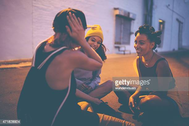 Teen girls sitting on street at night talking and laughing