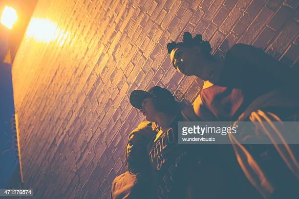 Teen Mädchen stehen unter Licht gegen die Wand bei Nacht