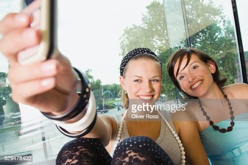 Teen girls taking pictures with cell phone : Stockfoto