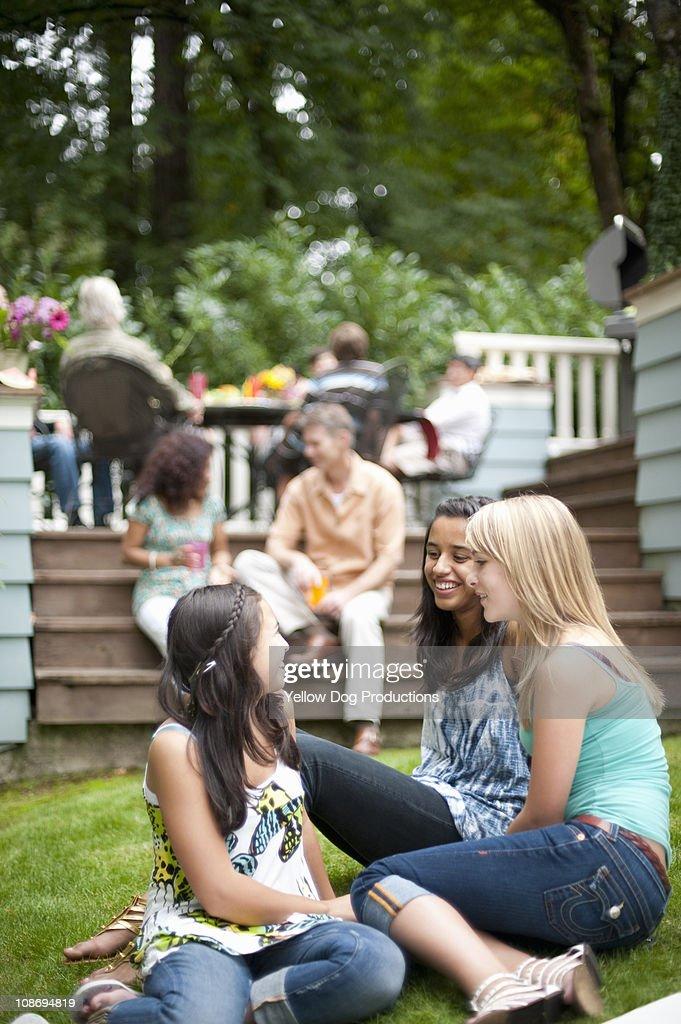 Teen girls talking at neighborhood barbecue : Stock Photo
