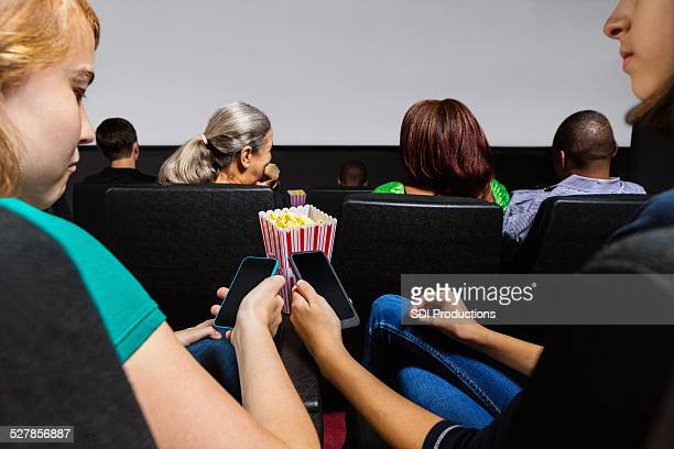 Teen girls texing with cell phones in movie theater