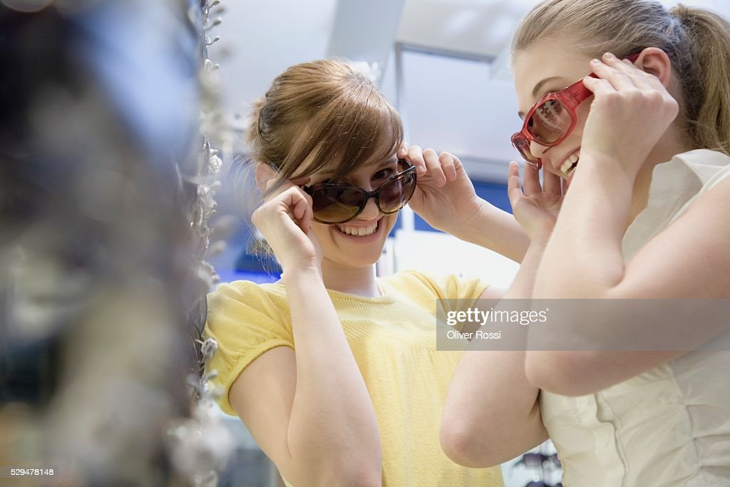 Teen girls trying on sunglasses : Bildbanksbilder