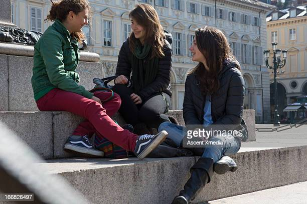 Teen girls use have conversation, urban piazza