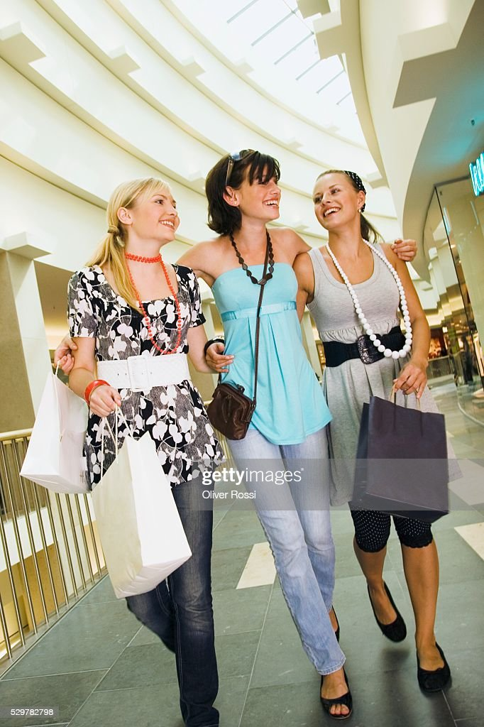 Teen girls walking together in shopping center : Stock Photo
