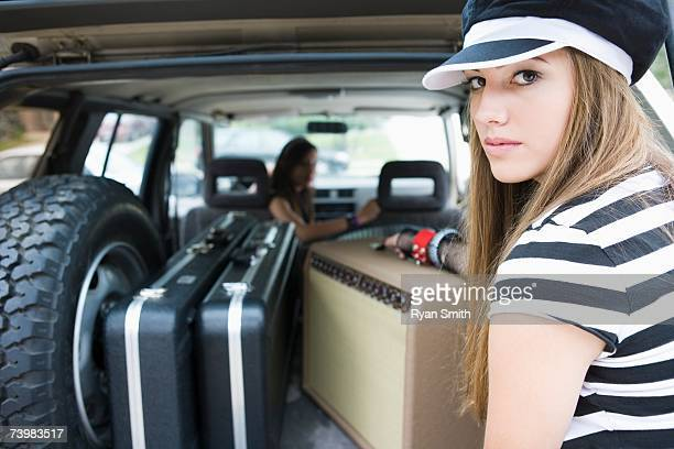 Teen girls with guitar cases and amplifier in vehicle