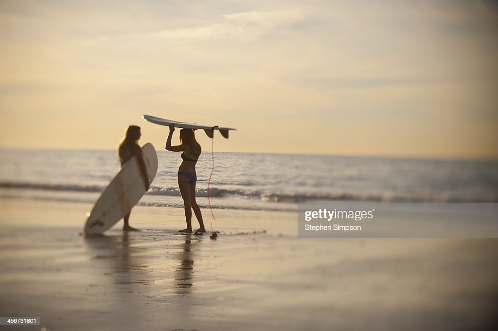 teen girls with surfboards discussing the day : Stock Photo