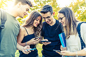 Teen group of friends with smartphones at park. Millennials using mobile phones, addicted to technology and social media. Lifestyle and friendship concepts