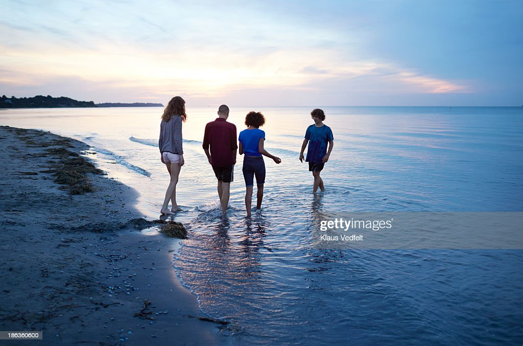 Teen group paddeling in the ocean at sunset