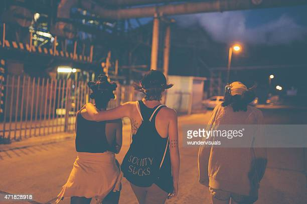 Teen grunge girl friends walking on urban road at night