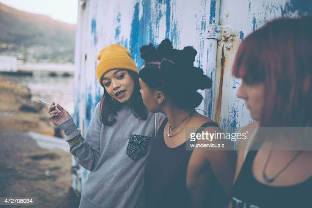 Teen grunge girl smoking and talking with her friends