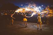 Teen grunge girls dancing with firework flares at night