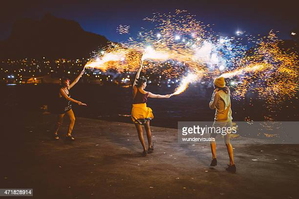 Teen grunge girls dancing with firework flares at night