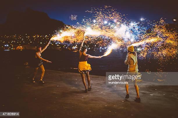 Teen grunge Niñas bailando con fuego artificial exacerbaciones por la noche