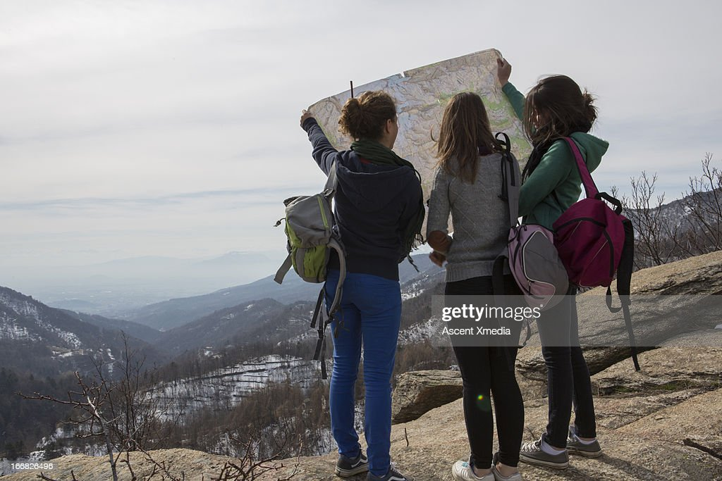 Teen hikers look at map on rock knoll above valley