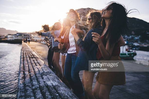 Teen hipster friends dancing on the pier at sunset