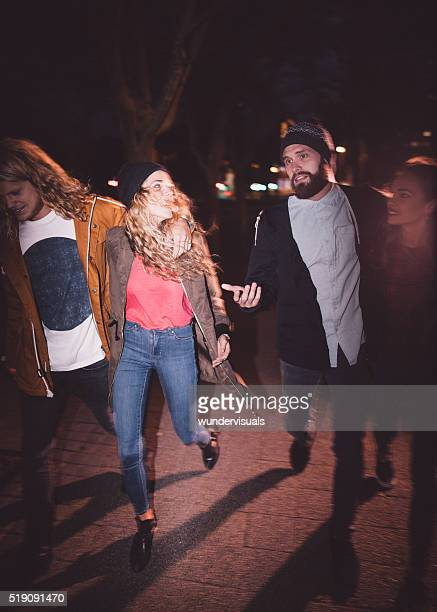 Teen hipster friends enjoying a night walk in the city