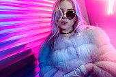 Teen hipster girl in stylish glasses and fur posing on street neon light wall background, female teenager fashion model woman with beautiful face looking at camera in city night light glow, back to 80