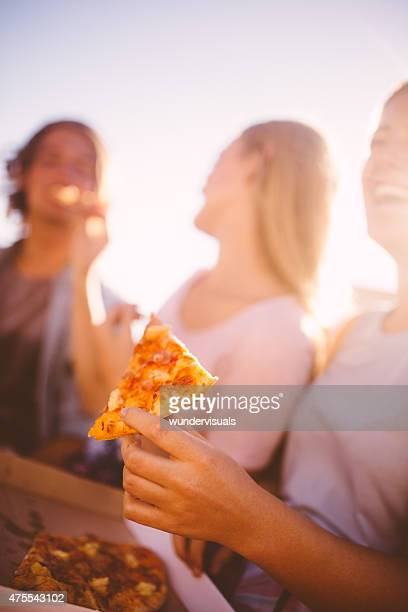 Teen holding a slice of pizza with friends in background