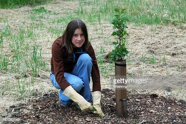 A teen is weeding an Oak outside