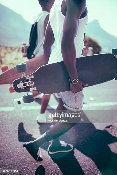 Teen longboarders caminhar juntos a olhar fresco