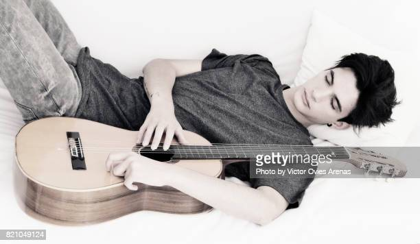 Teen male sleeping lying on a sofa embracing his guitar