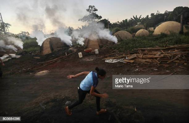 A teen runs past as smoke rises while Amazon wood scraps are burned for charcoal in a deforested section of the Amazon on June 26 2017 near Ariquemes...