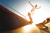 Teen skater hang up over a ramp on a skateboard in a skate park. Wide angle