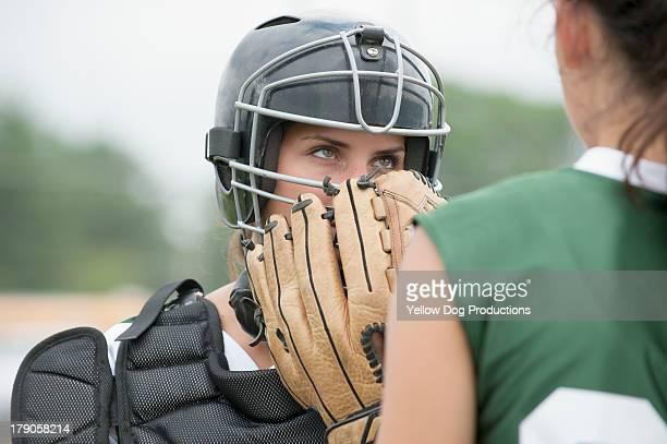 Teen Softball Catcher talking to Pitcher