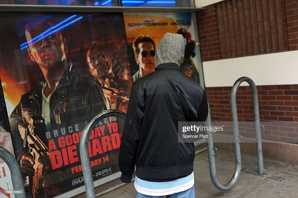 A teen stands in front of posters advertising new action films at a Brooklyn movie theater on January 11, 2013 in New York City. Following the shootings of children at a elementary school last month in Connecticut, numerous politicians and activists have begun to focus on violence in video games and films. US vice-president Joe Biden is meeting with games industry representatives today to discuss graphic violence, often with guns, in many of today's most popular video games. The administration is also expected to address violence in the film industry as well.