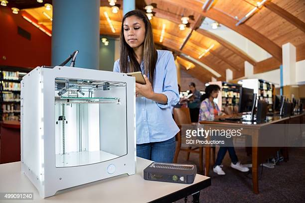 Teen student uploading design to 3D printer from digital tablet