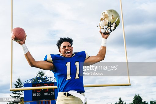 Teenage American football player celebrating victory on soccer pitch