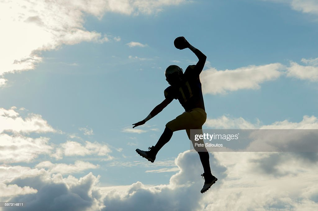 Teenage american football player, jumping with ball, mid air