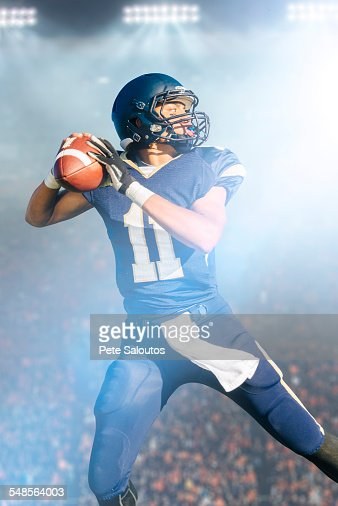 Teenage American football player jumping with ball