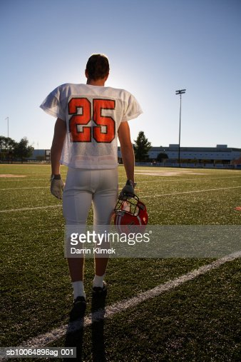 Teenage (16-17) American football player standing in playing field, rear view