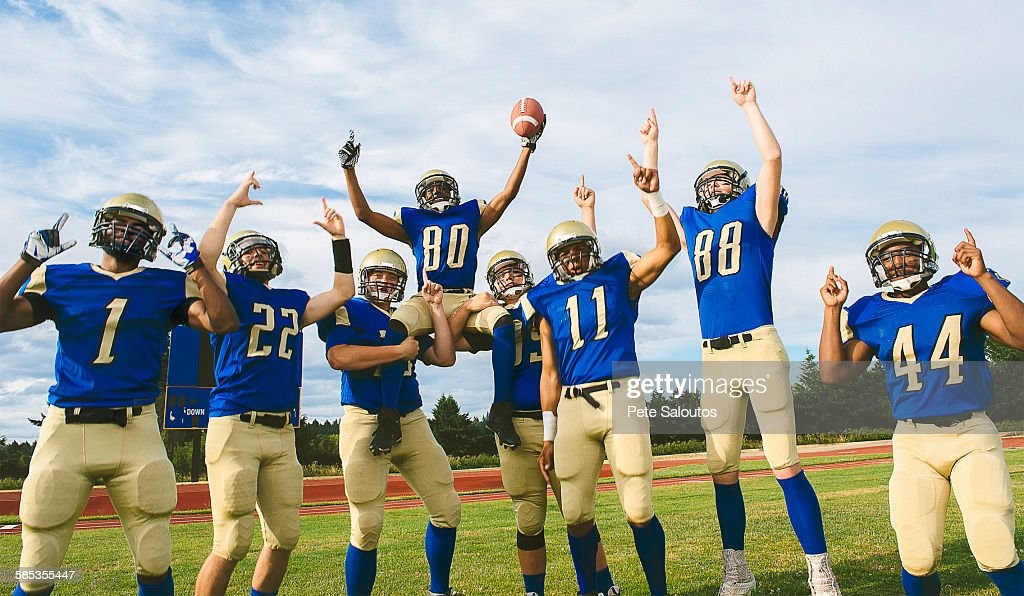 Teenage and young male American football team celebrating on soccer pitch